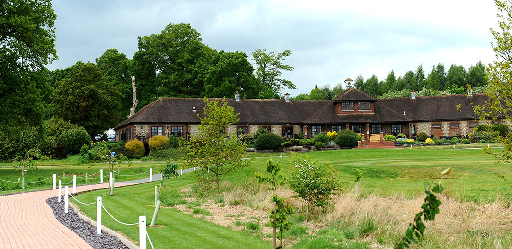 A picture of the popular Surrey wedding venue Reigate Hill Golf Club taken from across the greens and the path leading from the outdoor Waterside venue