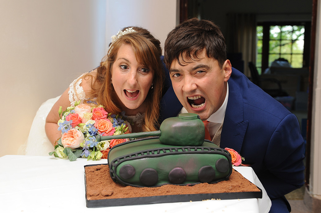 The Bride and Groom pictured in The Clarence Suite at Reigate Hill Golf Club in Surrey prepare to take a bite out of their alternative and unusual Tank wedding cake