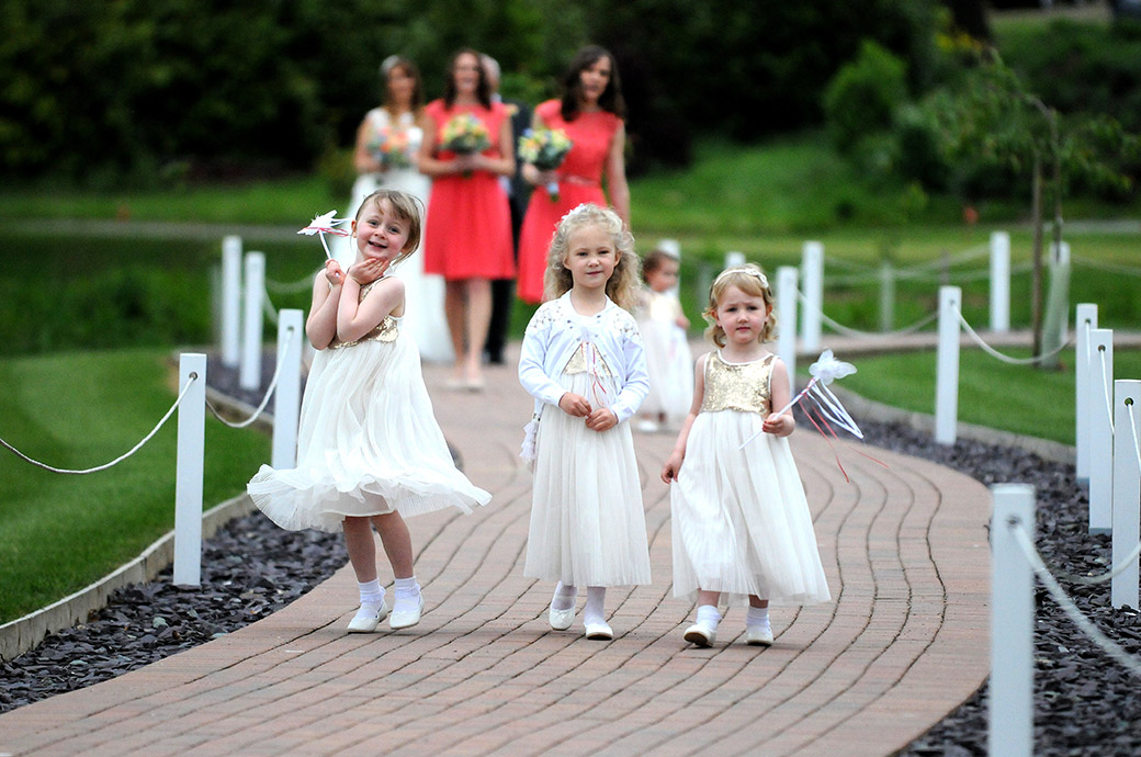 Cute bridesmaids at Surrey wedding venue Reigate Hill Golf Club in white and with butterfly wands have fun as they lead the wedding procession down the meandering Waterside path