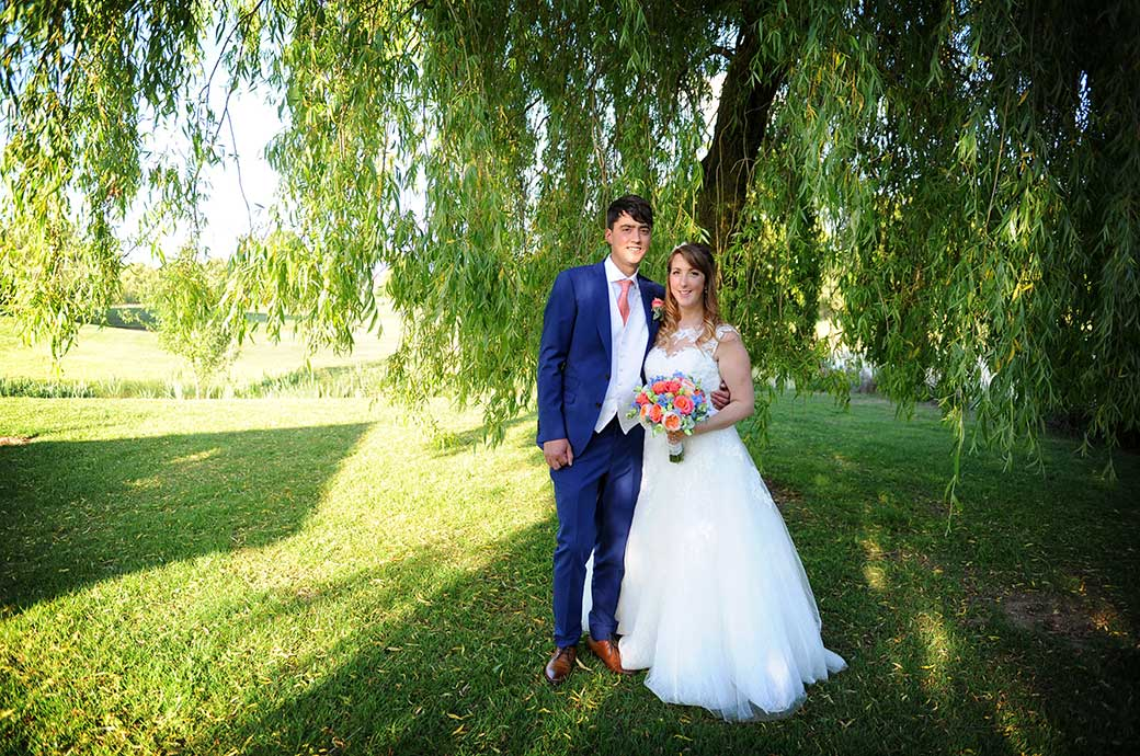 Happy smiling young newlyweds stand together beneath a tree out of the sun in the lovely green and scenic grounds at Reigate Hill Golf Club in Surrey