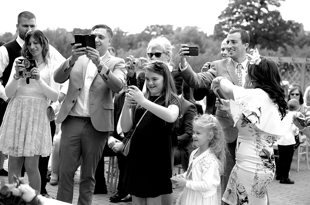 Smiling family and guests get out their phone cameras to capture the young newlyweds signing the marriage register at the outside Waterside venue at Reigate Hill Golf Club in Surrey