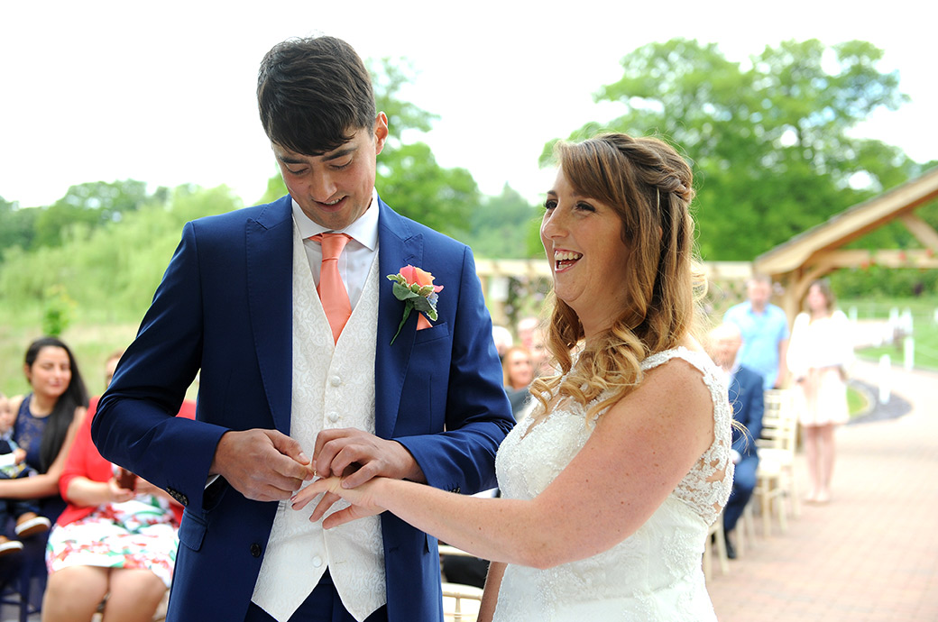 Bride laughs as the Groom struggles to get the wedding ring onto her finger at Surrey wedding venue Reigate Hill Golf Club at the atmospheric outside Waterside venue