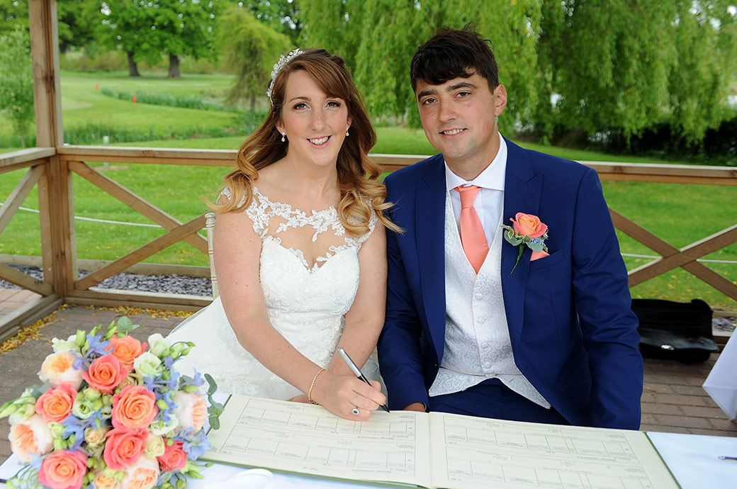 All smiles for the happy newlywed couple as the happy Bride poses signing the marriage register at Surrey wedding venue Reigate Hill Golf Club's outside Waterside space