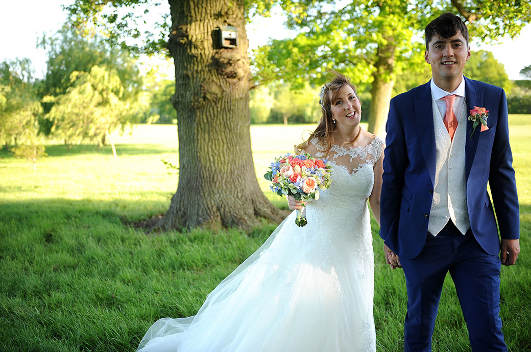 Excited and happy looking Bride and Groom captured by a Surrey Lane wedding photographer as they walk across the grass at Reigate Hill Golf Club in Gatton Bottom