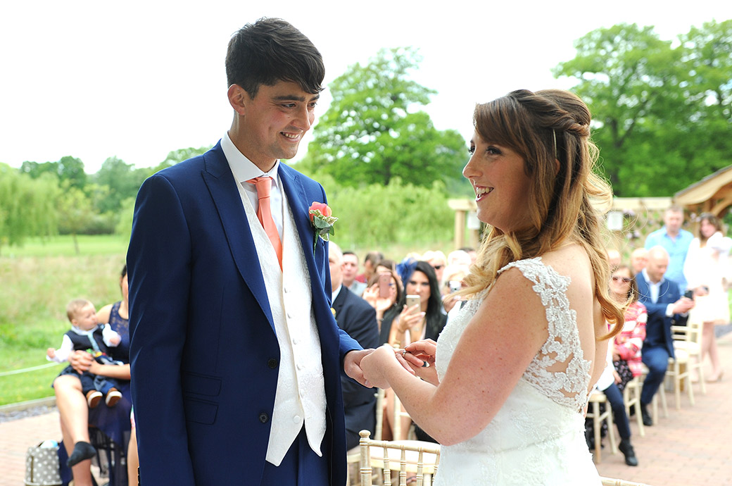 Happy and smiling Bride and Groom as the Bride says her marriage vows during an outdoors service at the Waterside venue at Reigate Hill Golf Club in Gatton Bottom Surrey