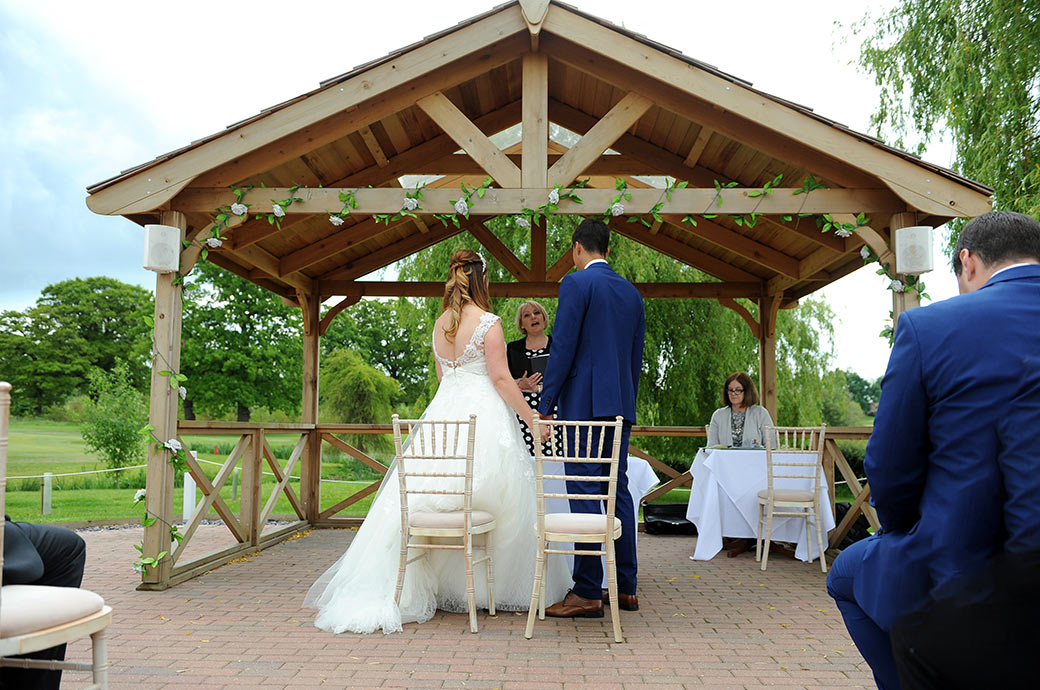 The marriage service ends and the registrar announces the Bride and Groom as husband and wife at the outside Waterside venue at Surrey wedding venue Reigate Hill Golf Club