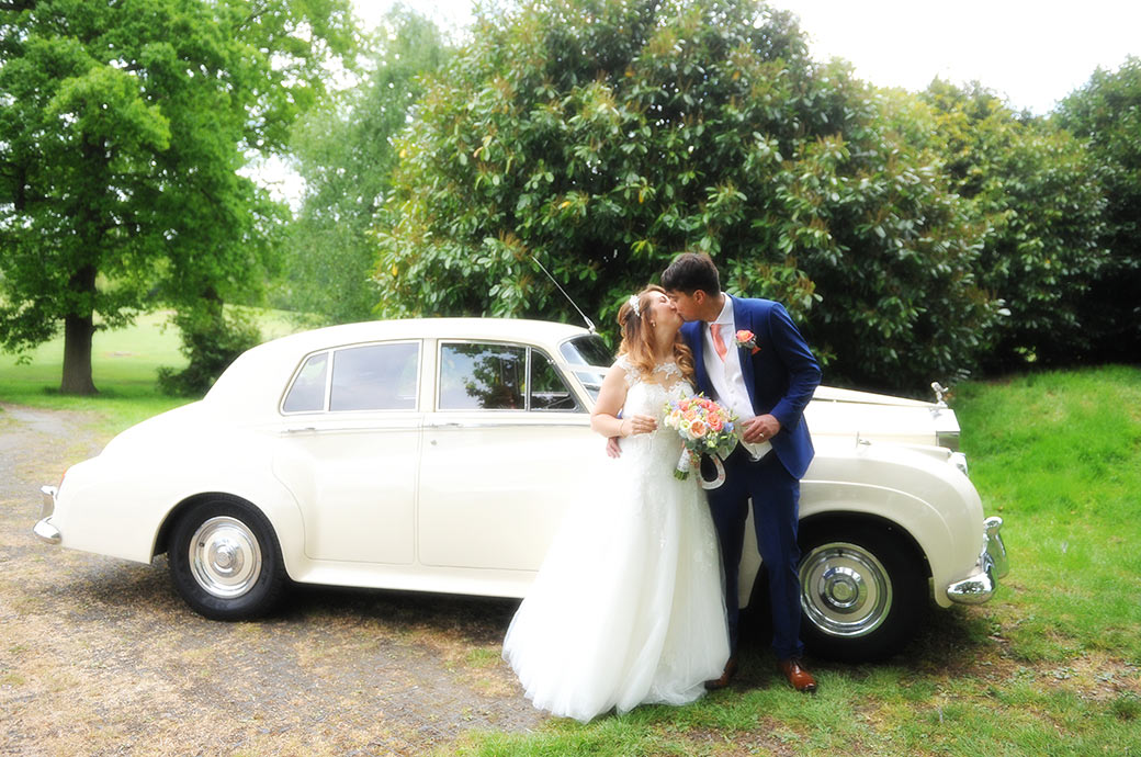 Young lovers captured at Surrey wedding venue Reigate Hill Golf Club kiss in front of their beautiful white Roll Royce Silver Shadow wedding car