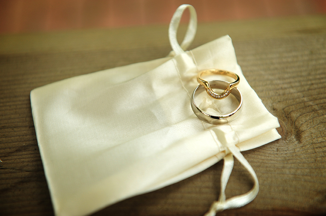Glistening and shiny wedding rings resting on a draw bag captured just before the marriage ceremony at Surrey wedding venue Reigate Hill Golf Club at the outdoor Waterside venue