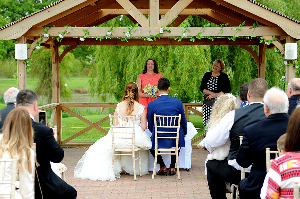 Wedding photo of a bridesmaid delivering a reading to the Bride and groom during the marriage ceremony at the lovely outside Waterside venue at Reigate Hill Golf Club Surrey