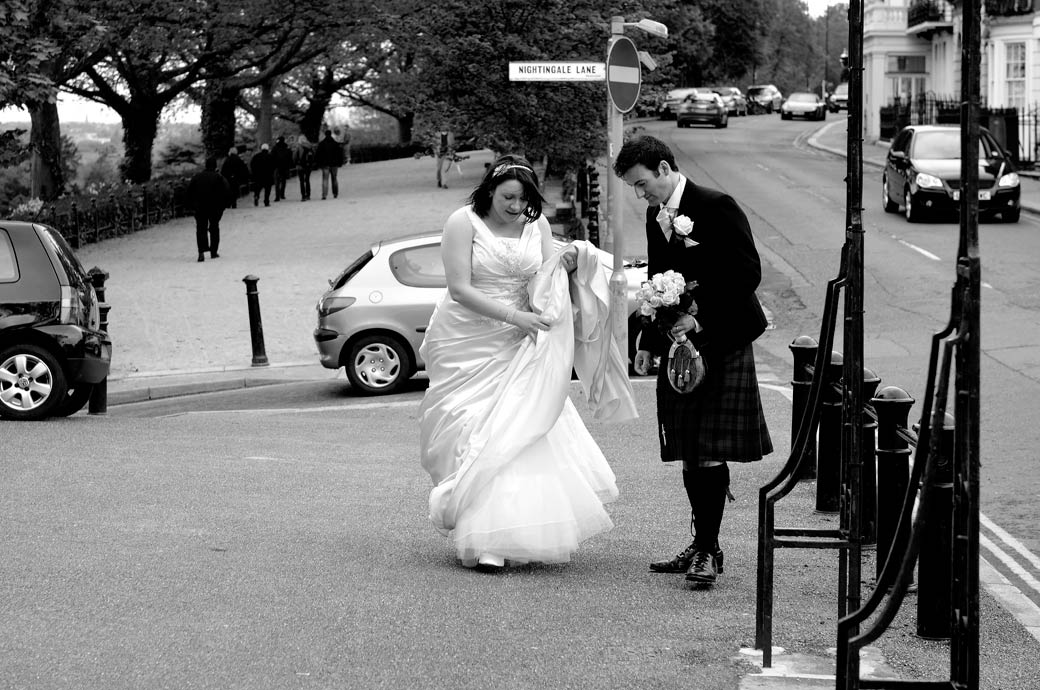 Bride sorts out  her wedding dress whilst Groom holds her bouquet taken on the street opposite Richmond Gate Hotel wedding venue in Surrey