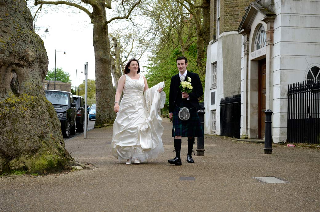 A wedding photo of a happy bride walking as her husband holds her wedding bouquet over the road from Richmond Gate Hotel, Surrey