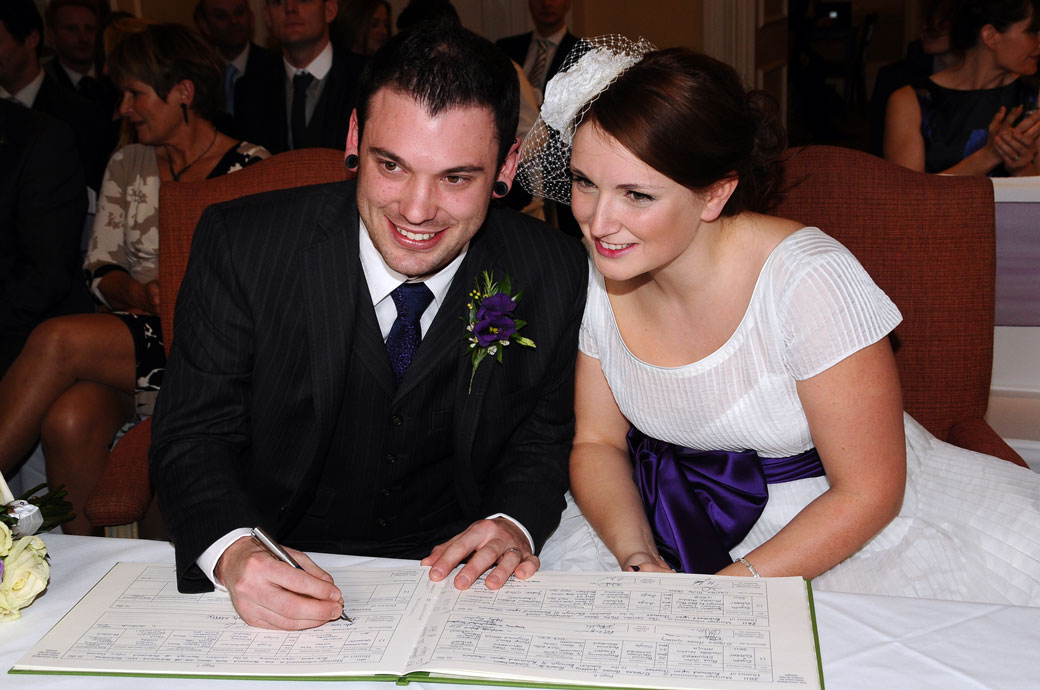 A Richmond Gate Hotel wedding photograph of the happy smiling Bride and Groom as the Groom signs the marriage register