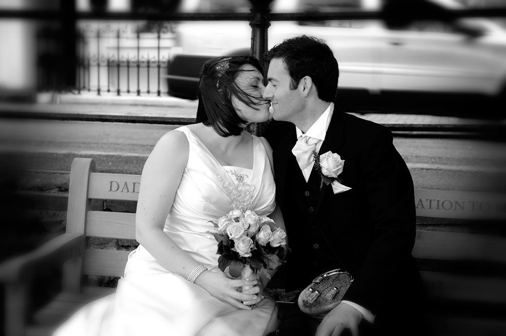 Atmospheric and romantic black and white kiss on the bench photograph taken over the road from Richmond Gate Hotel Surrey wedding venue