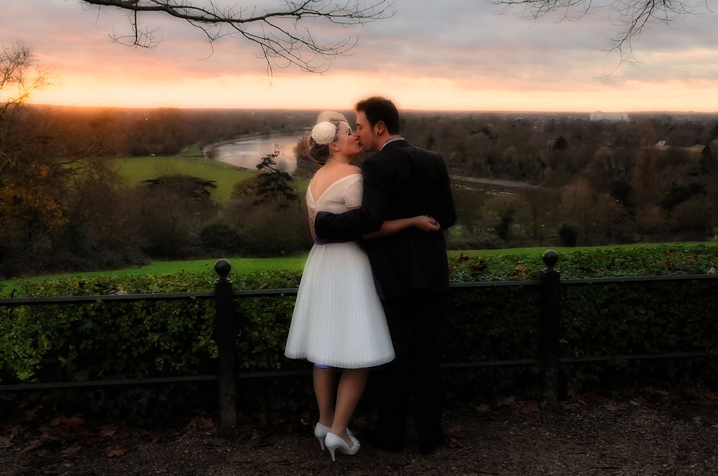 A romantic wedding couple kiss as the sun sets over the road from their wedding venue at Richmond Gate Hotel Surrey