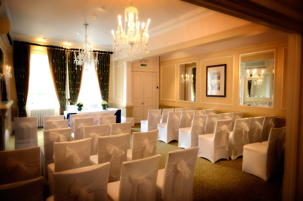 A picture of the Terrace wedding room dressed in white seat covers and white bows at Surrey wedding venue Richmond Gate Hotel