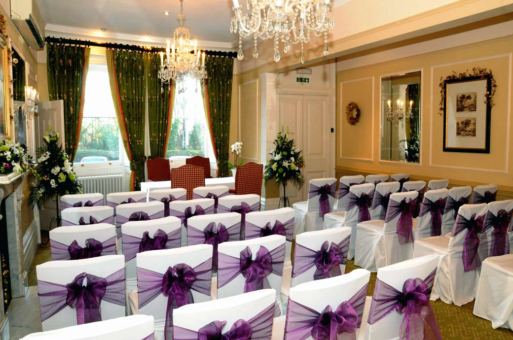 A Terrace Room wedding photograph dressed in white seat covers and mauve bows at Surrey wedding venue Richmond Gate Hotel