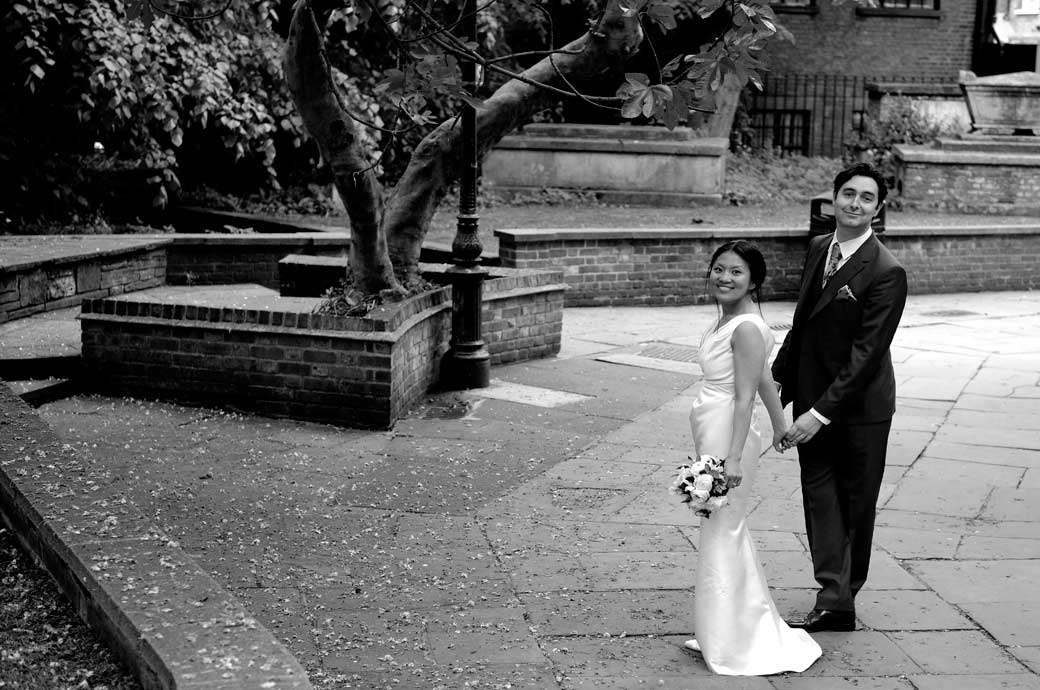 A lovely wedding pictures of a happy couple glancing over with big smiles after having got married at Richmond Register Office Surrey