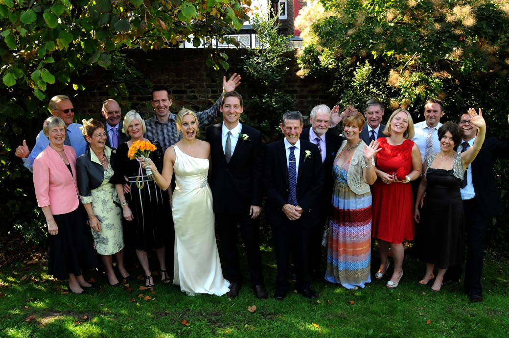 A fun happy wedding photo of everyone waving taken in the back garden at Richmond Register Office by Surrey Lane wedding photographers