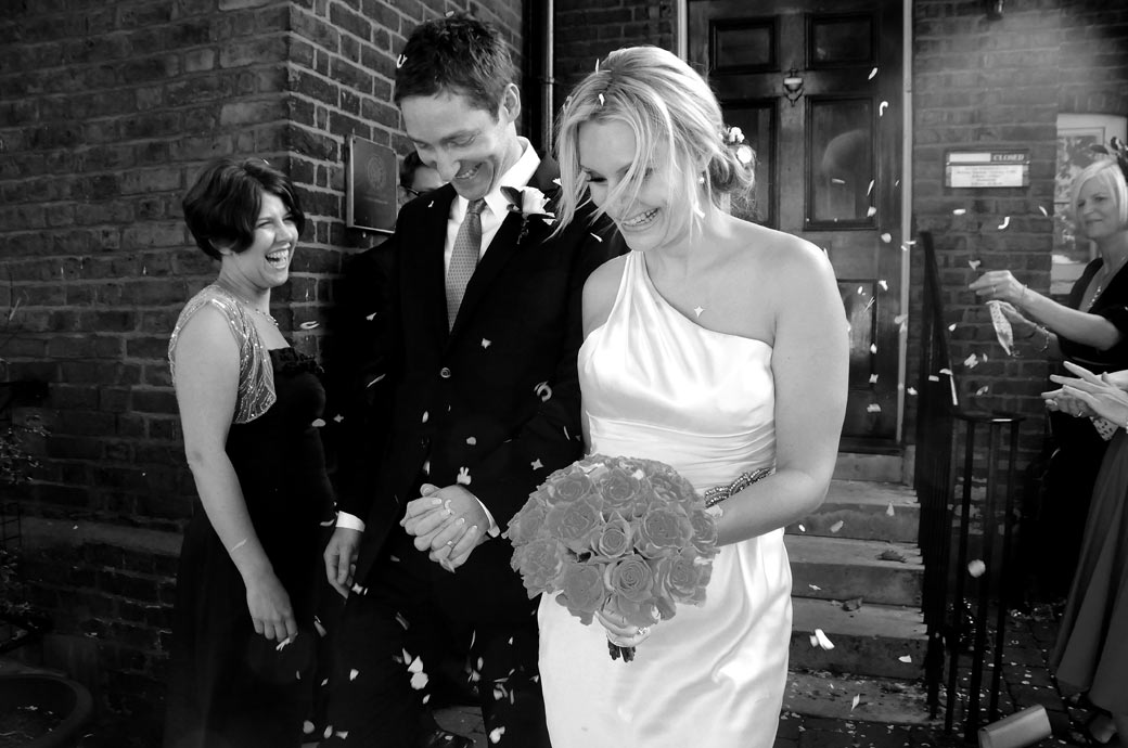 A happy, laughing wedding confetti throwing shot of the couple on the steps outside the Surrey wedding venue Richmond Register Office