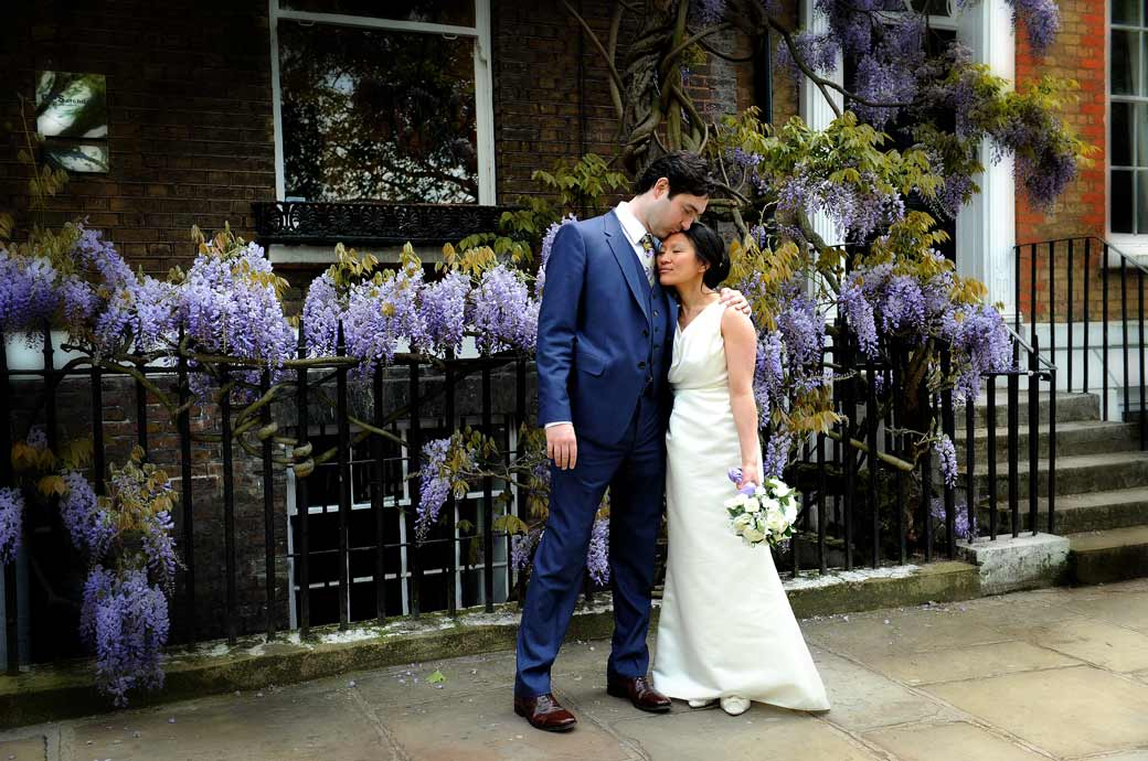 A tender loving embrace by the beautiful mauve Wysteria photo captured in Richmond Surrey after a wedding at Richmond Register Office