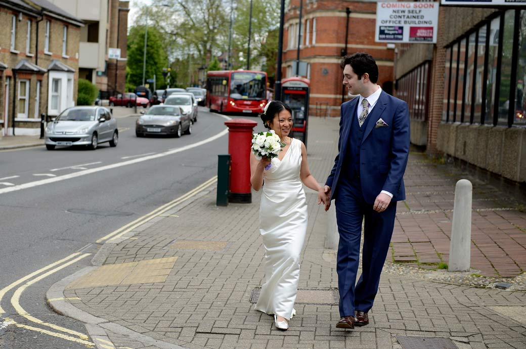 A lovely wedding photograph of the Bride and Groom happily walking down the road as husband and wife from Richmond Register Office, Surrey