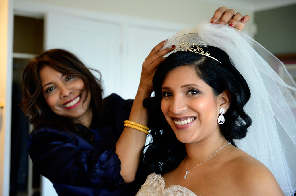 Smiling Mother puts her daughter's veil on in this lovely happy wedding photograph taken at Surrey Wedding venue Selsdon Park Hotel, Croydon