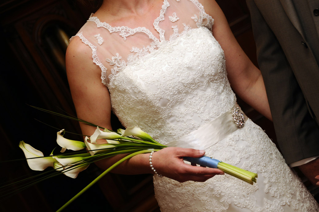 Close up wedding photograph of the Bride holding her lily bouquet complete with pearl bracelet and silver sash buckle at the popular Selsdon Park Hotel in Croydon Surrey