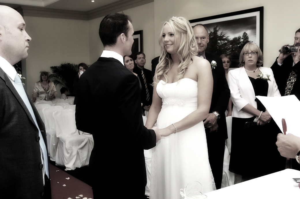 Smiling Bride holds the hands of the Groom and looks into his eye as he says his marriage vows captured in this Selsdon Park Hotel wedding photo taken in Croydon Surrey