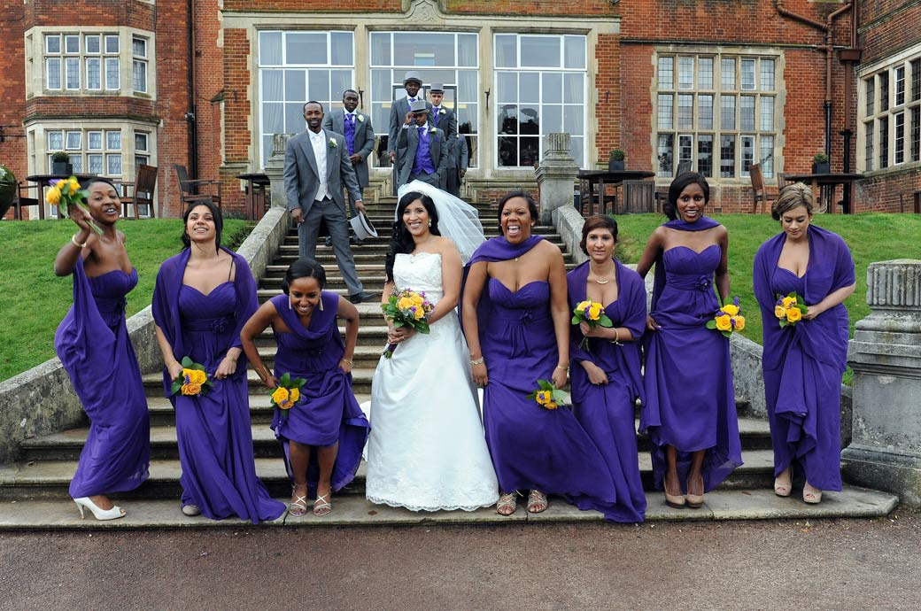In purple dresses the Bridesmaids standing with the Bride on the steps at Selsdon Park Hotel in Croydon Surrey getting ready to jump into the air for a fun wedding photo