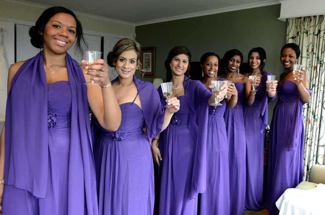 Lovely Bridesmaids all dressed in purple raise their glasses of champagne in celebration in the Bridal room at Selsdon Park Hotel, Croydon a popular Surrey wedding venue