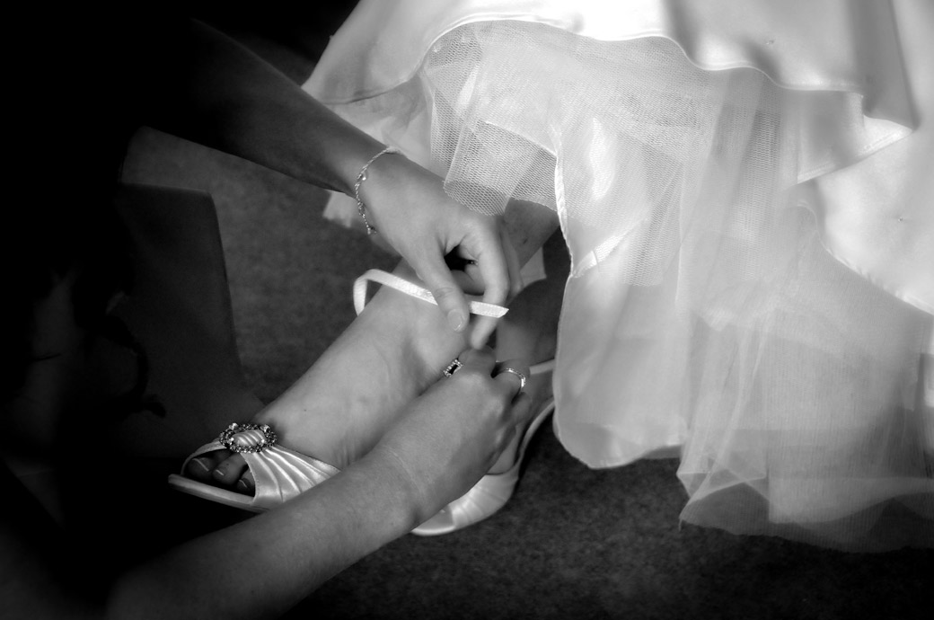 Beautifully delicate wedding picture of the Bride's shoe being fastened taken at the Selsdon Park Hotel wedding venue Croydon by Surrey Lane weddings