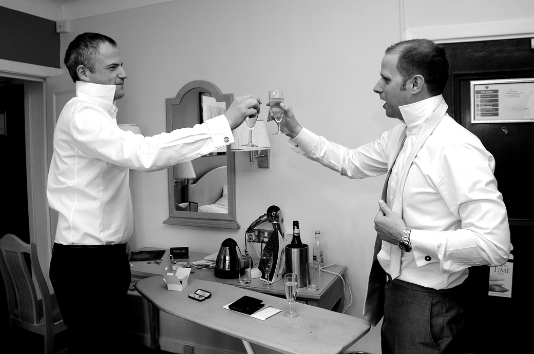 Groom and Best Man celebrate with champagne as they get ready for the wedding at Selsdon Park Hotel, Croydon captured by Surrey Lane wedding photographers