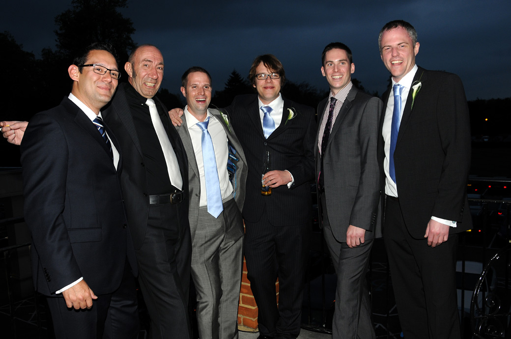 Groom enjoying himself with the boys in this wedding photo taken out on the balcony at Selsdon Park Hotel in Croydon Surrey during the nighttimes' celebrations