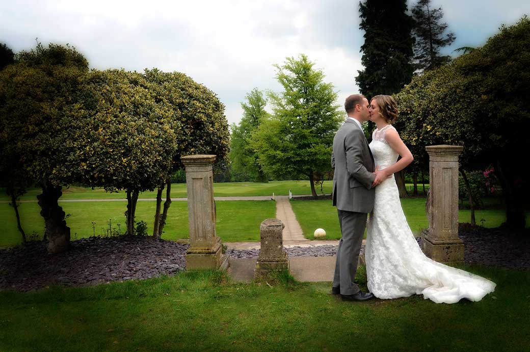 A romantic wedding picture of newly-weds having a kiss in the lovely green and peaceful grounds of Selsdon Park Hotel Croydon Surrey wedding venue