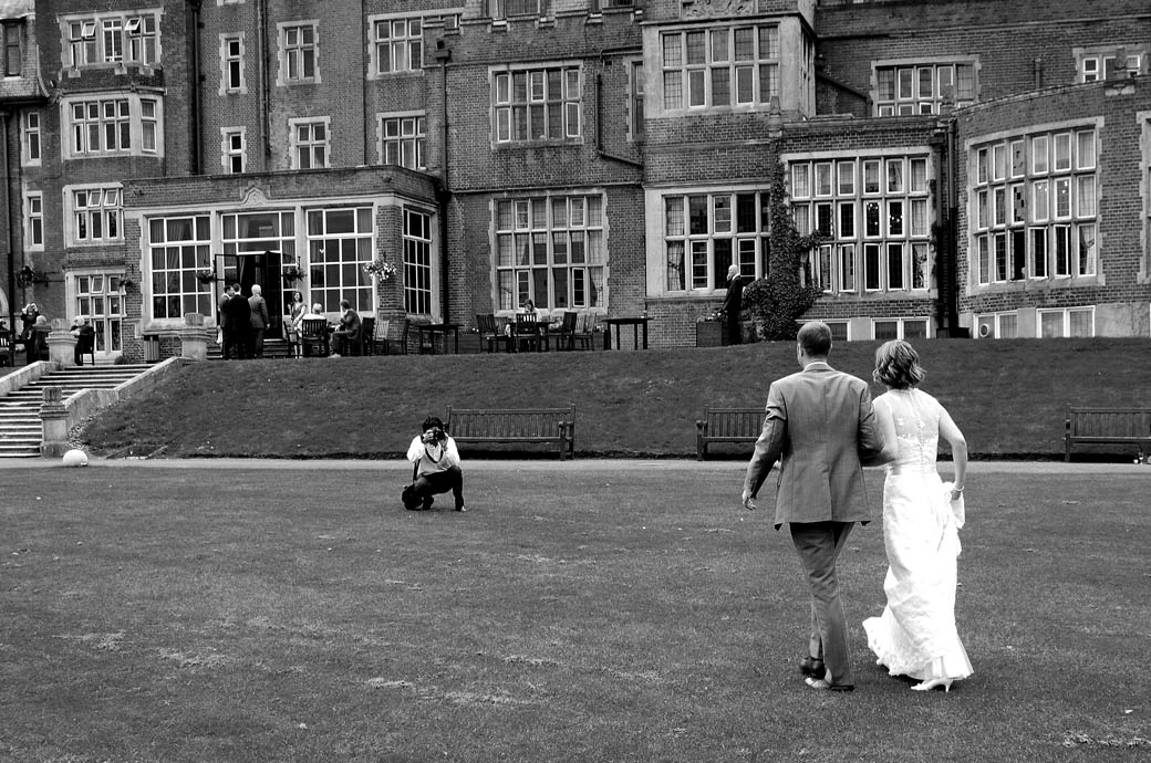 Bride and groom ay Selsdon Park Hotel, Croydon walking back across the lawn arm in arm towards the Surrey Lane wedding photographer taking pictures of them