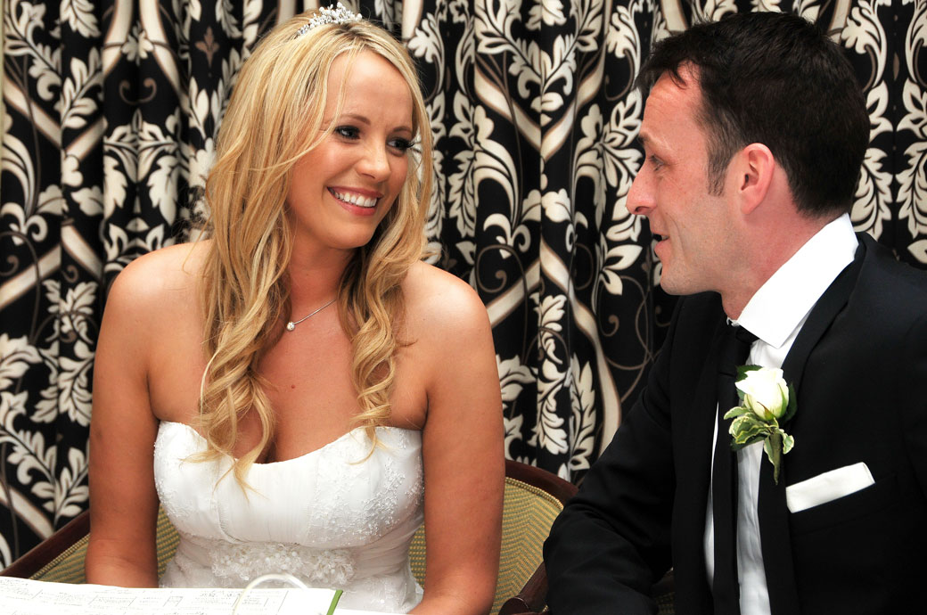 Beautiful Bride smiles at her husband after getting married at a popular Surrey wedding venue in Croydon in this Selsdon Park Hotel wedding picture