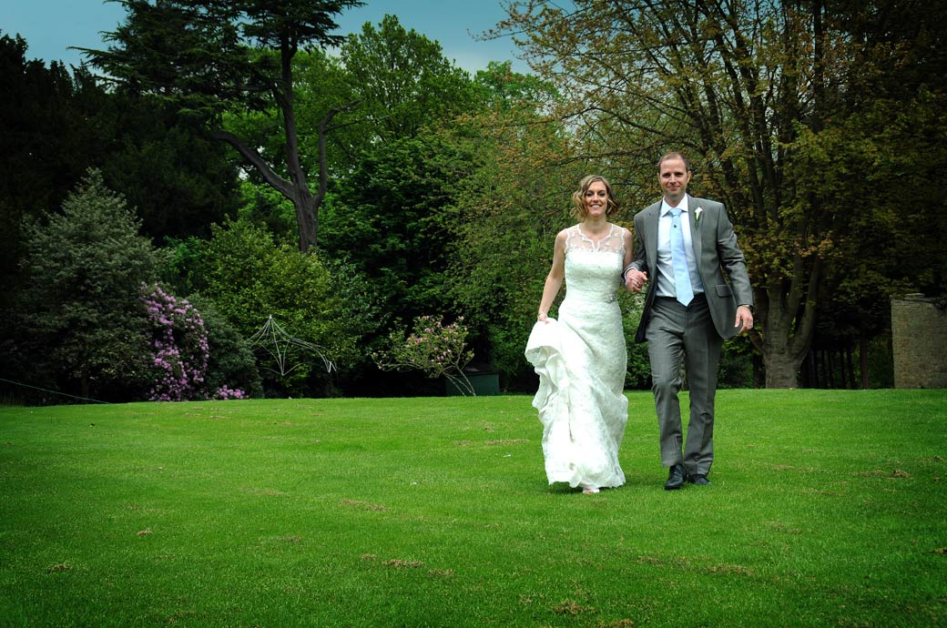Smiling newlywed couple holding hands as they walk across the lush green lawn at the sprawling Surrey wedding venue Selsdon Park Hotel which has a history of over a 1000 years