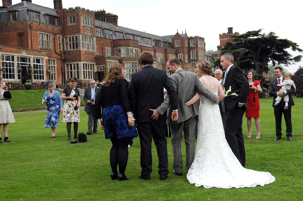Groom cheekily pinches a male guests bottom in this funny wedding photo taken in this line up on the lawn at Surrey wedding venue Selsdon Park Hotel