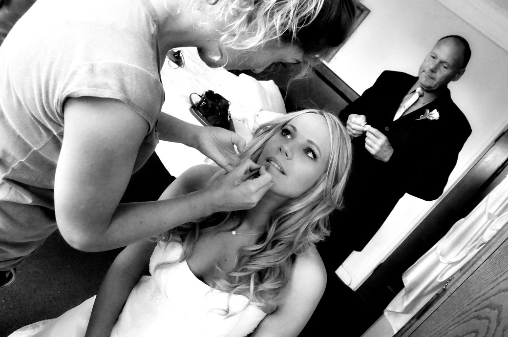 Beautiful looking Bride having her lipstick applied in one of the many rooms at the Selsdon Park Hotel, Croydon captured by a Surrey Lane wedding photographer