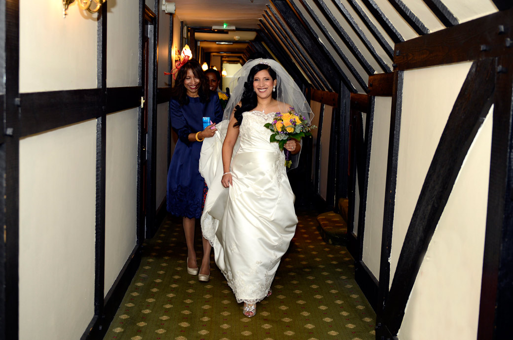 A beaming Bride helped by her mother walks down a reputedly haunted corridor at Selsdon Park Hotel a Surrey wedding venue with an ancient and fascinating past