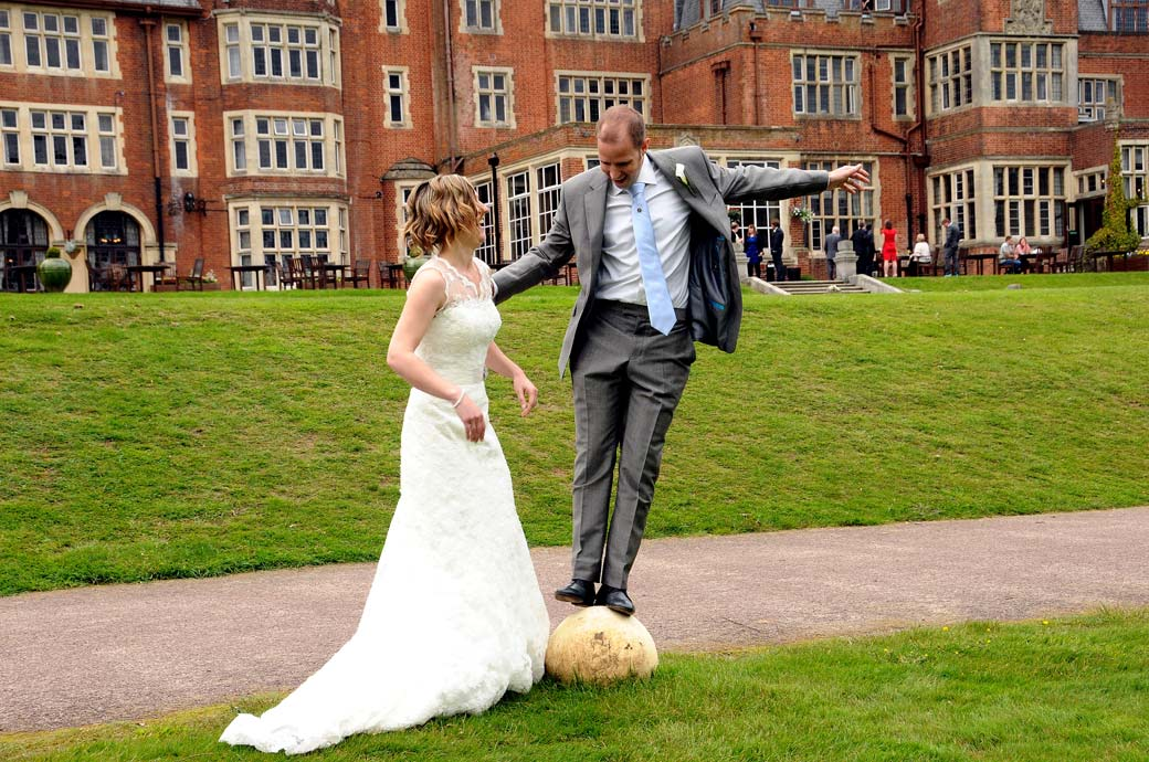 Wedding photograph of the bride laughing at the Groom as he balances on a  stone ball by the lawn at Selsdon Park Hotel a surrey wedding venue with a rich history of entertainment