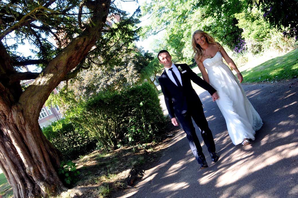 Wedding photo of a smiling Groom walking hand in hand with his lovely Bride along a shaded path in the relaxing grounds of Selsdon Park Hotel in Croydon Surrey