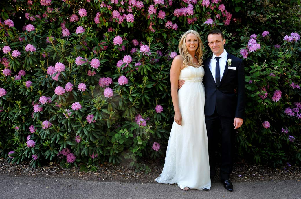 Happy Bride and groom standing before the colourful Rhododendrons bush in this wedding picture in the relaxing grounds of Surrey wedding venue Selsdon Park Hotel