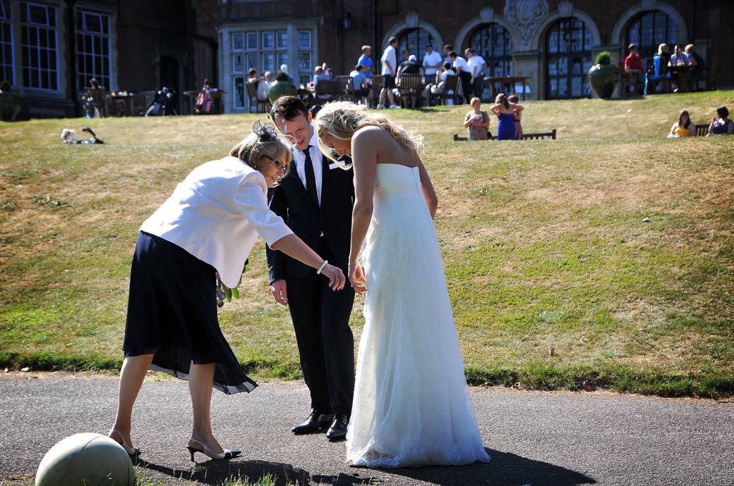 Guest helps Bride to adjust her beautiful wedding dress as she walks along the path at Selsdon Park Hotel Surrey during her romantic walk time with her husband