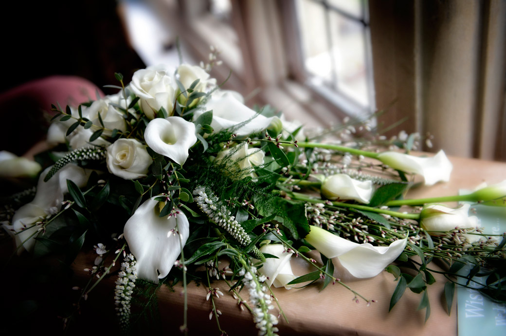 A beautiful wedding bouquet of white lilies and roses sits on the window sill of the bridal suite before a marriage ceremony at Selsdon Park Hotel, Croydon Surrey