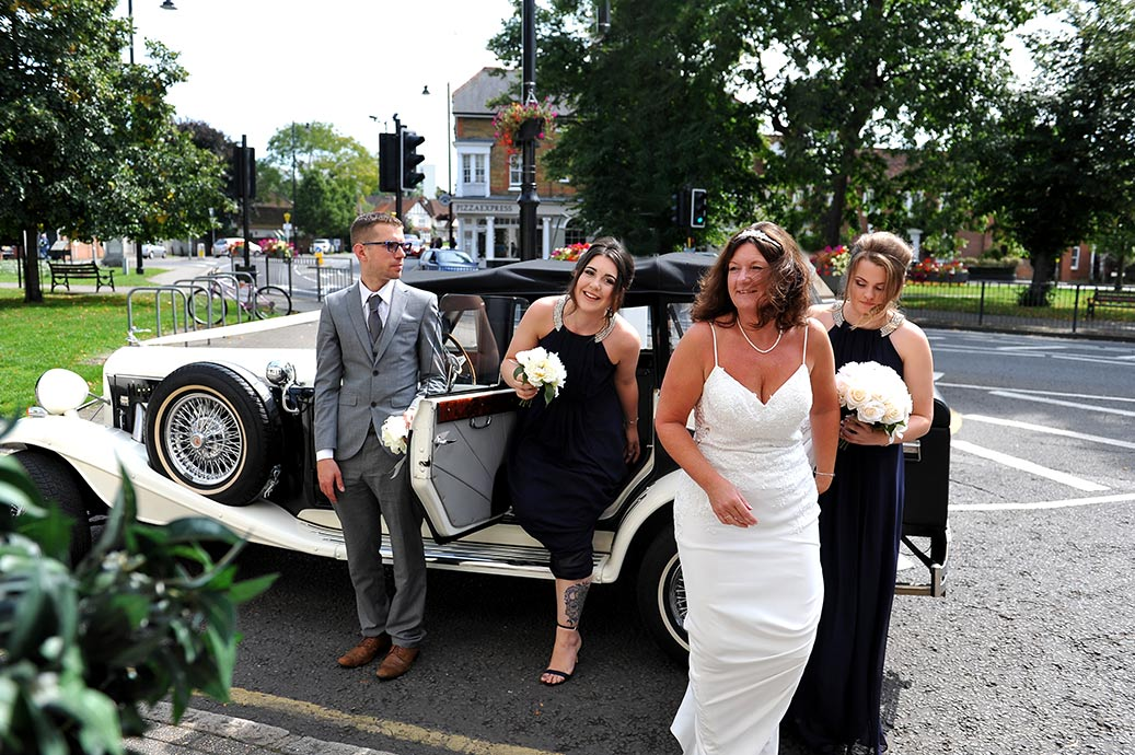 Smiling excited Bride with her Bridesmaids arrive in their white wedding car at wedding venue Great Western Ship Hotel in Weybridge Surrey
