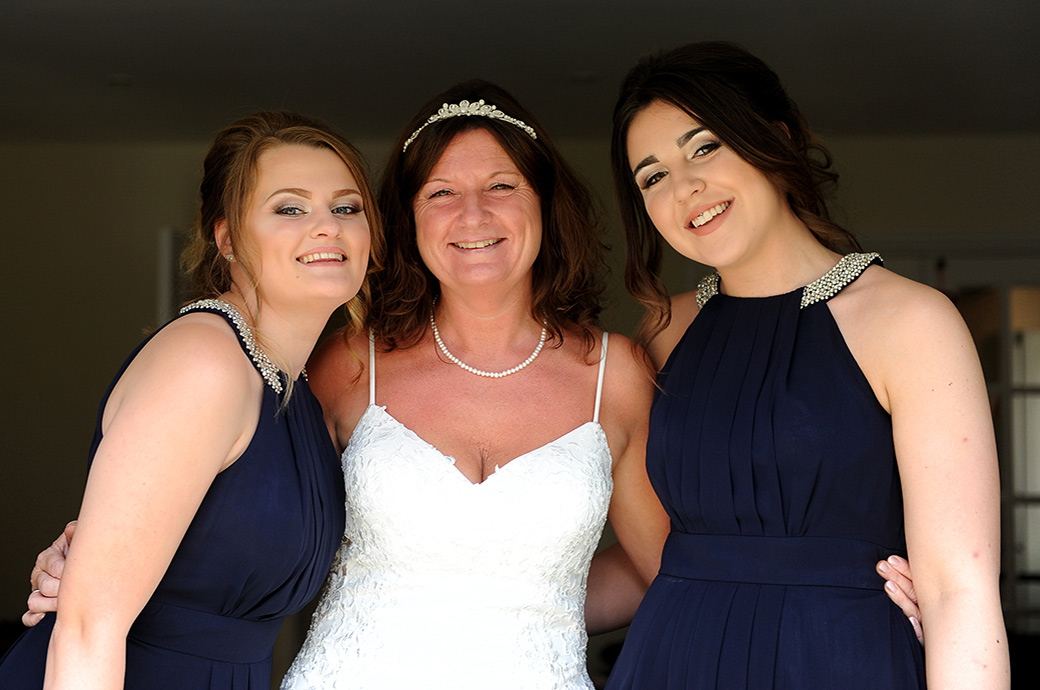 Smiling Bride and her daughter bridesmaids dressed and ready to leave for a wedding at the Great Western Ship Hotel in Weybridge in Surrey