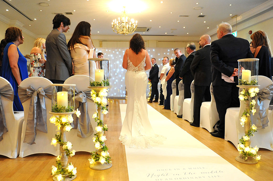 Wedding photograph of a Bride at Great Western Ship Hotel in Weybridge Surrey walking down the aisle of the brightly dressed Thames Suite alone
