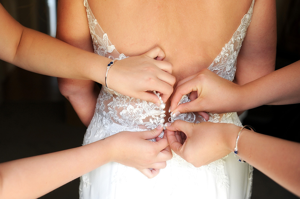 Atmospheric wedding photograph of Bridesmaids' hands fastening up a Bride's wedding dress at Surrey venue Great Western Ship Hotel in Weybridge