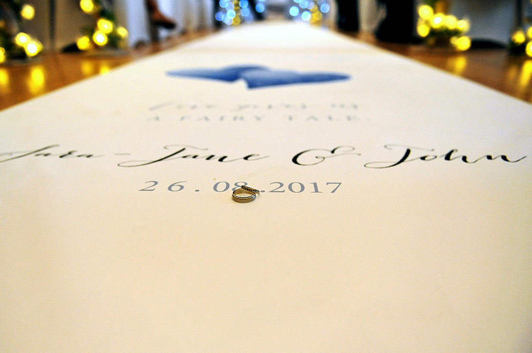 Wedding rings pictured at The Great Western Ship Hotel in Weybridge in The Thames Suite and placed on a personalised white paper aisle runner